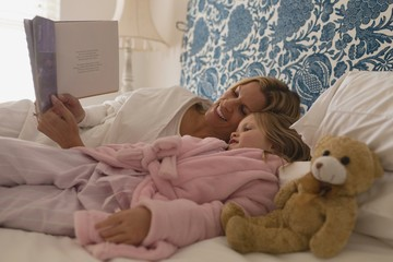 Mother with her daughter reading storybook in bedroom