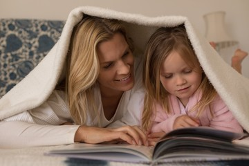 Mother with her daughter reading storybook under blanket in
