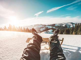 Pov view of young man looking the sunset on snow high mountains with vintage wood sledding