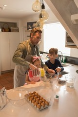 Father with his children preparing food in kitchen