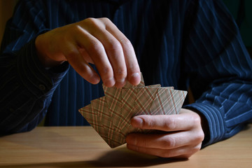 Man in darkness holding a set of playing cards and chooses one of them, business strategic competition concept