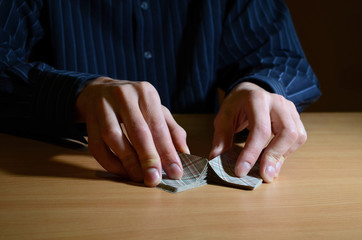 Man in darkness holding a set of playing cards and shuffling them, business strategic competition concept