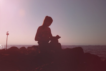 Silhouette of a girl sitting on the rocks near the sea, working on a laptop
