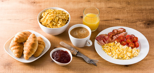Breakfast with scrambled eggs, bacon, tomatoes,coffee,orange juice ,croissant and corn flakes on wooden table. Panoramic view