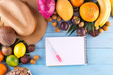Summer composition. Tropical palm leaves, hat, many fruits on blue wooden background. Concept shopping list for summer travel