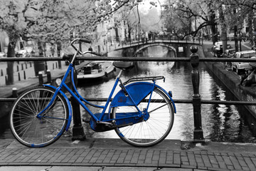 A picture of a lonely blue bike on the bridge over the channel in Amsterdam. The background is black and white.