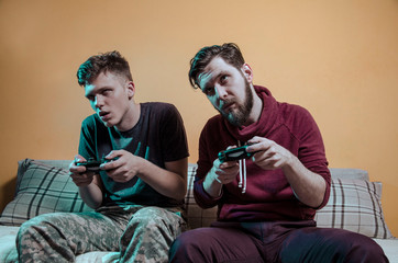 Zombie like video gamers indoors at home holding game controllers