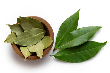 Dried bay leaves in a dark wood bowl next to fresh bay leaves isolated on white from above. Wall mural
