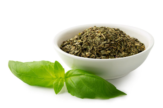 Dried chopped basil in white ceramic bowl next to fresh basil leaves isolated on white.