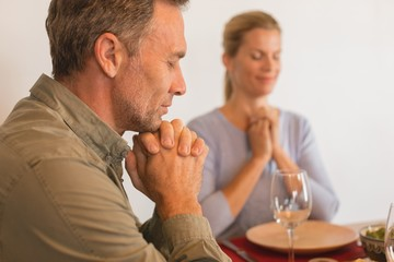 Couple praying before having food on dining table