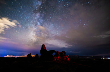 Milky Way breaking through clouds over Turret Arch, Arches National Park