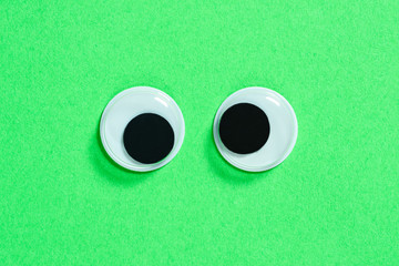 Mad googly eyes on neon green background. Cross-eyed funny toys eyes close up.