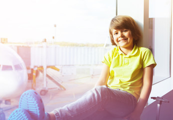 Boy sitting next to window and looking at airplane