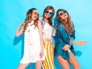 Three young beautiful smiling hipster girls in trendy summer colorful clothes. Sexy carefree women in sunglasses isolated on blue. Positive models going crazy