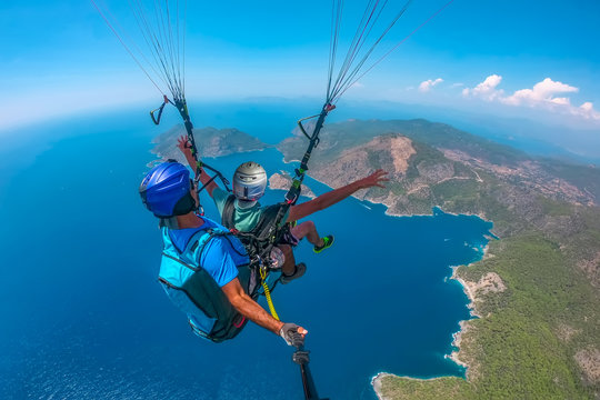 Ölüdeniz    Paragliding in the sky. Paraglider tandem flying over the sea with blue water and mountains in bright sunny day. Aerial view of paraglider and Blue Lagoon in Oludeniz, Turkey. Extreme spor