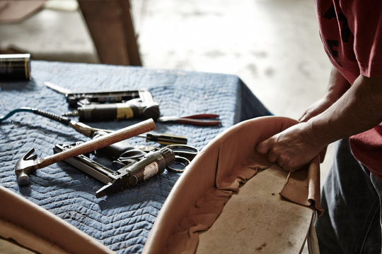 craftsman working leather upholstery