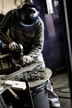 worker in metal shop using hammer