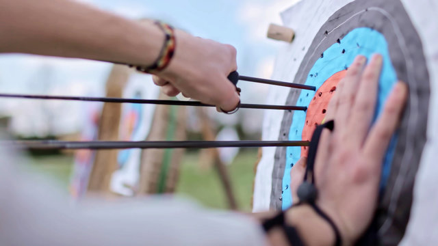 Archer pull out arrows from bullseye