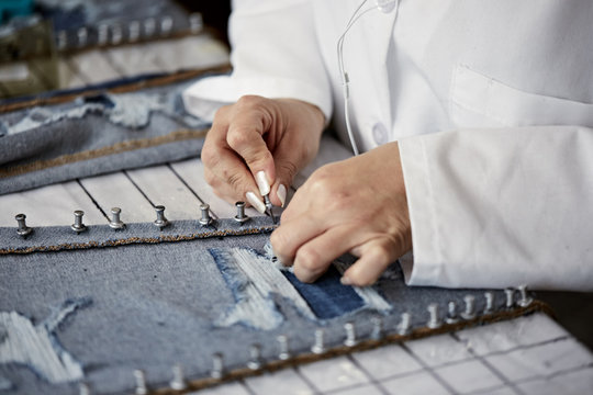 Female worker in white coat pinning distressed jeans to board