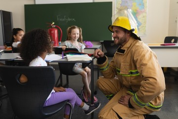 Side view of male firefighter teaching schoolkids about fire