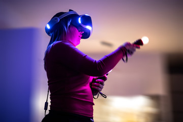 The girl is playing on the console in VR game -  Virtual Reality