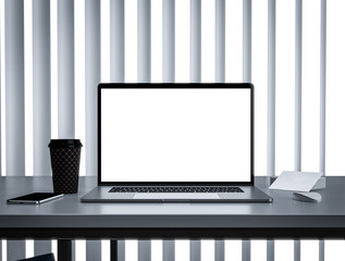 Laptop with blank screen on table in office interior building - mockup, template