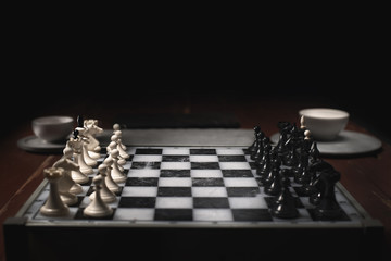 Chess pieces on the chessboard. Dark background and smoke.