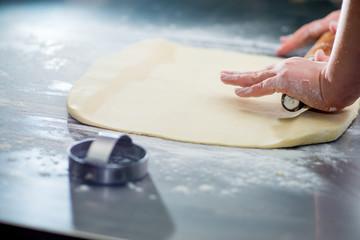 baker's female hands rolling dough