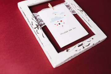 Valentines day card in the white frame on the red background photographed from the side