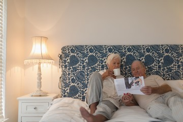 Senior couple reading newspaper in bedroom