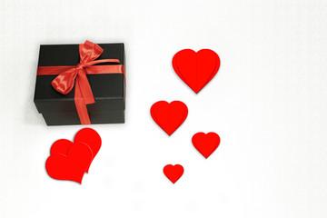 Czarne pudełko z czerwoną wstążką i sercami na białym tle.