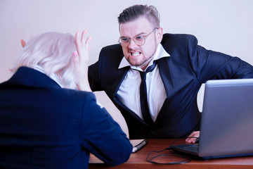 Fototapeta Furious  boss man screaming agressively at female worker. Stress, work, conflict, scandal concepts. Horisontal image. obraz