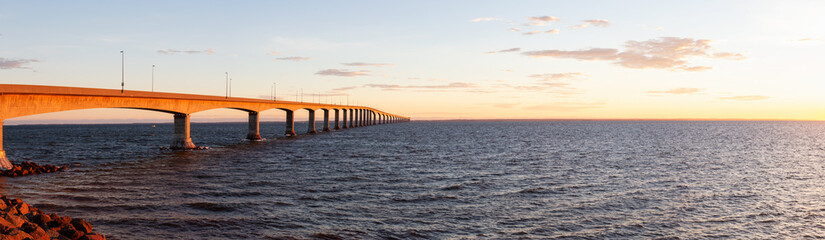 Panoramic view of Confederation Bridge to Prince Edward Island during a vibrant sunny sunrise. Taken in Cape Jourimain National Wildlife Area, New Brunswick, Canada. Fototapete