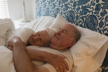 Senior couple sleeping together in bedroom