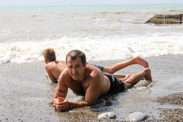 A man and a child are resting on the seashore, sea foam and waves.