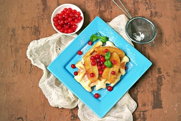 Dessert, homemade biscuit waffles with fried bananas and red currant berries on a blue plate. Top view, copy space.