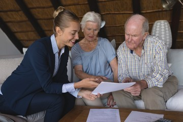 Female doctor and senior couple discussing over medical reports