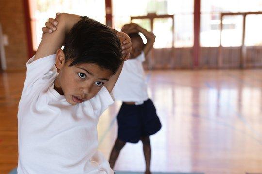 Schoolboy doing yoga on a yoga mat in school