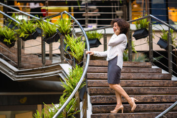 Asian woman talking on phone standing on the steps outdoors.