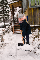 Cute girl cleans snow to shovel near the country house.