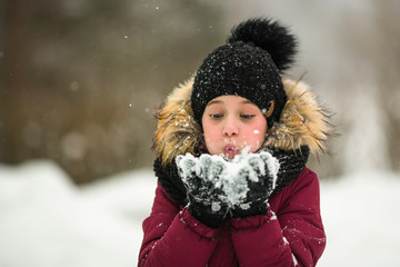 Little girl blowing on snow in hands at amazing winter.