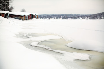 Frozen river covered with ice and snow in the village.