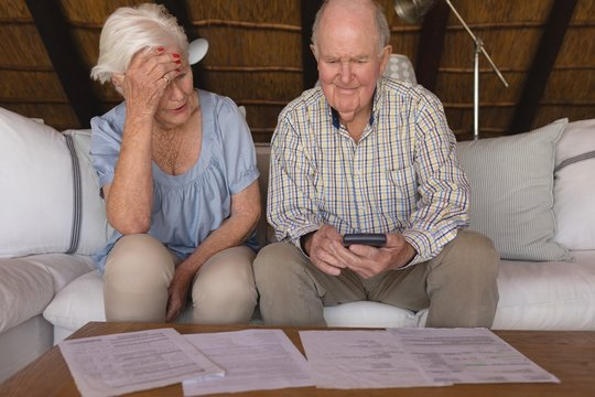Worried senior couple discussing over medical bills