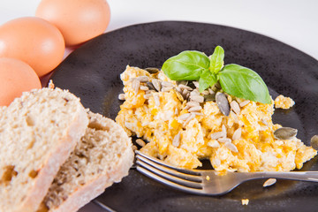 Scrambled eggs with sunflower and pumpkin seeds, some fresh eggs and wholemeal bread, eaten with a fork, decorated with basil, on a white background