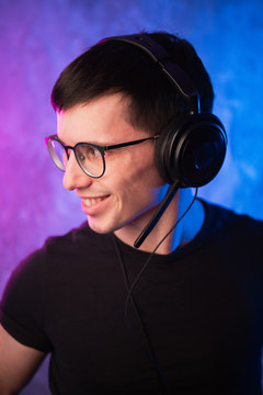 Gamer or streamer in earphones with microphone over colorful pink and blue neon lit wall