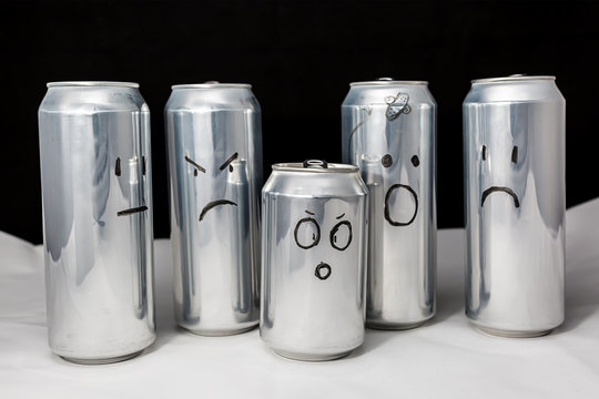 Concept of different emotions of diverse people. Emoji on open and empty aluminium cans. Emoticons