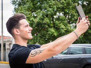 Portrait of young attractiave man in business suit using tablet PC to take selfie photo outside in city street