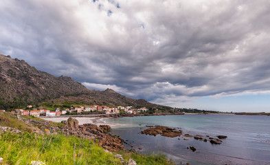 Beauty Atlantic coast with cliff, beach, ocean, village and sky with clouds. Galicia, Spain.