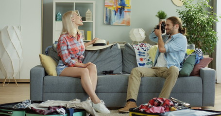 Young handsome Caucasian man taking photos on the camera of his pretty young wife who posing on the couch at home among mess as their packing their stuff for the trip.