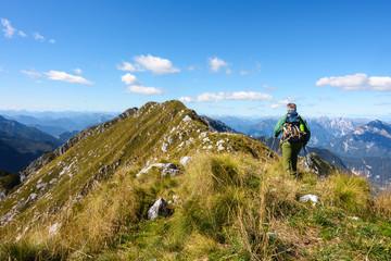 Man hiker walking on top of mountain against blue sky.